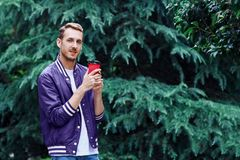 Man in the forest against green tree background with cup of coffee. Young smiling man wearing the purple blazer is drinking coffee from red cup in the forest royalty free stock photos