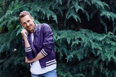 Man in the forest against green tree background. Young smiling man wearing the purple blazer in the forest standing against green tree background crosses his royalty free stock image