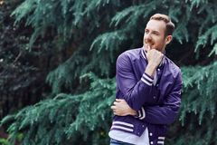 Man in the forest against green tree background. Young smiling man wearing the purple blazer in the forest standing against green tree background crosses his stock photography