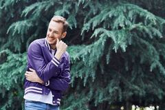 Man in the forest against green tree background. Young smiling man wearing the purple blazer in the forest standing against green tree background crosses his stock photo