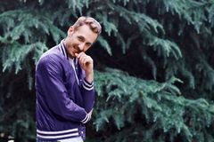 Man in the forest against green tree background. Young smiling man wearing the purple blazer in the forest standing against green tree background crosses his royalty free stock photo