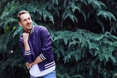 Man in the forest against green tree background. Young smiling man wearing the purple blazer in the forest standing against green tree background crosses his stock photos