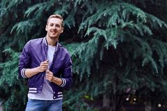 Man in the forest against green tree background. Young smiling man wearing the purple blazer in the forest standing against green tree background holding his royalty free stock photos