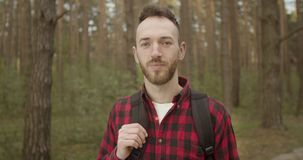Man in Forest. Portrait of young bearded tourist man dressed in red checked shirt with backpack in the forest stock footage