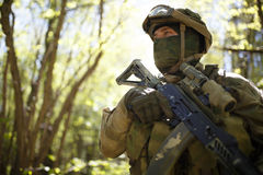 Man in forest on reconnaissance. Military man in forest on reconnaissance by day stock image