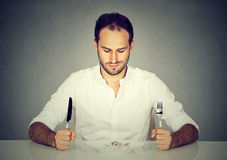 Man with fork and knife sitting at table looking at empty plate. Man with fork and knife looking at empty plate royalty free stock photo