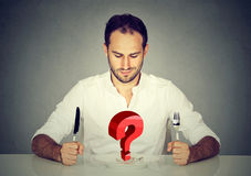 Man with fork and knife sitting at table looking at plate with big red question. Young man with fork and knife sitting at table looking at empty plate with big Stock Images