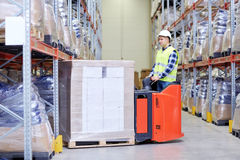 Man on forklift loading boxes at warehouse Stock Images