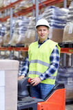 Man on forklift loading boxes at warehouse. Wholesale, logistic, loading, shipment and people concept - man or loader with forklift or loader loading boxes at Stock Photos