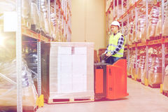 Man on forklift loading boxes at warehouse. Wholesale, logistic, loading, shipment and people concept - man or loader with forklift or loader loading boxes at Stock Images