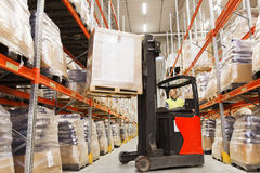 Man on forklift loading cargo at warehouse. Wholesale, logistic, loading, shipment and people concept - man or loader on forklift loading cargo at warehouse Stock Photo