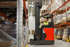 Man on forklift loading cargo at warehouse Stock Photo