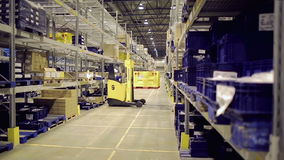 Man on forklift riding and loading cargo on rack. Man driving forklift and loading cargo on rack in warehouse
