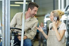 Man in forklift talking to female colleague stock photos