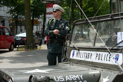 A man in the form of a military police. BERLIN - MAY 28: A man in the form of a military police car and Willys MB, the exhibition 125 car history - 125 years of Royalty Free Stock Images