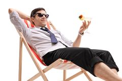 Man in formal clothes with a cocktail relaxing in a deck chair. Isolated on white background stock images