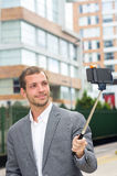 Man formal clothing posing with selfie stick in Royalty Free Stock Photography