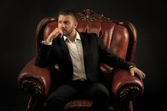 Man in formal outfit in leather chair on black background. royalty free stock photography