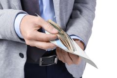 Man in formal suit counting money in envelope Stock Photos
