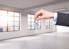 A man in formal suit holds a key in a modern loft panoramic apartment or office. Rent or buy new home or office. New York view. Royalty Free Stock Photo
