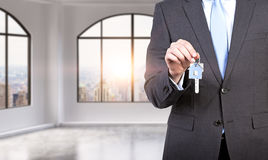 A man in formal suit holds a key in a modern loft panoramic apartment or office. Rent or buy new home or office. New York view. A Stock Photo