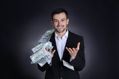 Man in formal suit with money on black background. Stock exchange broker Stock Images
