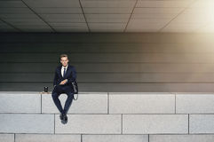 Man in formal suit sitting on wall Stock Photos