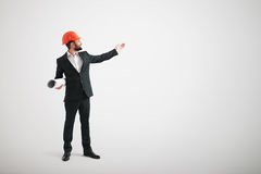 Man in formal wear and a construction helmet point his hand towa Royalty Free Stock Photos