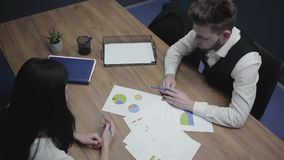The man in formal wear demonstrating papers with charts and schemas to his female colleague, sitting at the table. Shooting from the above, top view. Camera stock footage