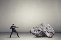 Man in formal wear pulling the big stone over light grey backgro Royalty Free Stock Photography