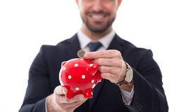 Man in formal wear put one euro coin into piggy bank. Isolated Stock Photo
