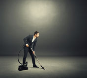 Man in formal wear vacuuming dark room Stock Images