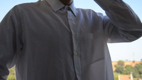 Man in Formal White Shirt Makes Call with his Smartphone Royalty Free Stock Photo