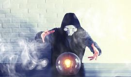 A man with a fortune teller ball. At the table royalty free stock photography