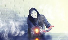 A man with a fortune teller ball. At the table royalty free stock photo