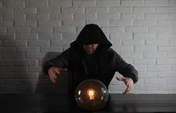 A man with a fortune teller ball. At the table stock images