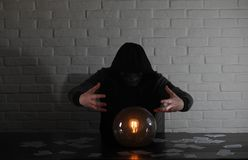 A man with a fortune teller ball. At the table stock image