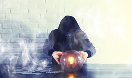 A man with a fortune teller ball. At the table stock photo