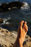 Man fot som kopplar av på ferier i en strand eller en sjö med havswaen Royaltyfria Bilder