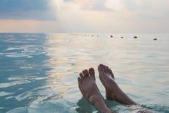 Man fot som svävar i havet på morgontid koppla av sommaren Fotografering för Bildbyråer