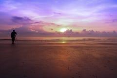 Man fotograferat soluppgånganseende på sanden Arkivfoto