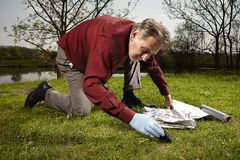 Man found falled meteorite on outdoor location. Man looking for falling meteorite made happy find on spring meadow Stock Images