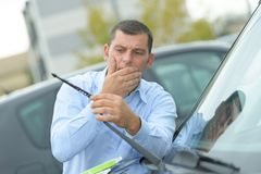 Man found out car wipers were broken Stock Photo