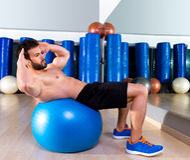 Man för Fitball buk- knastrandeSwiss boll på idrottshallen Fotografering för Bildbyråer
