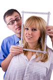 Man framing woman's face. Man using a ruler to form a picture frame around a woman's head.  White background Royalty Free Stock Image