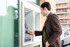 Man framställning av en kontant tillbakadragande från atm-bancomatservice arkivfoto