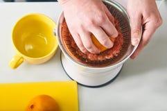 Man framställning av ny orange fruktsaft på köket Arkivfoton