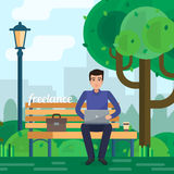Man freelancer works in park with computer on bench under tree. Stock Photos