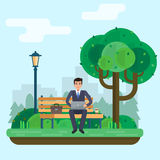 Man freelancer works in park with computer on bench under tree. Royalty Free Stock Photos