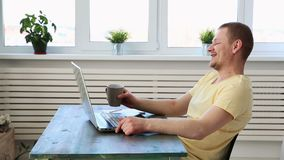A man freelancer works remotely at home on a laptop and communicates with colleagues in a video chat.  stock video footage